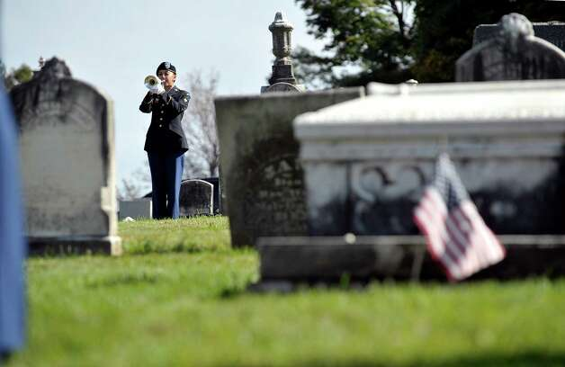 Specialist Taylor Kuchera, with the 53rd Troop Command of the New York Army National Guard, plays Taps during a presidential wreath laying ceremony at the gravesite of President Chester Arthur on Monday, Oct, 5, 2015, at the Albany Rural Cemetery in Menands, N.Y.  The event was held to honor President Arthur on his birthday.  (Paul Buckowski / Times Union) Photo: PAUL BUCKOWSKI / 10033591A