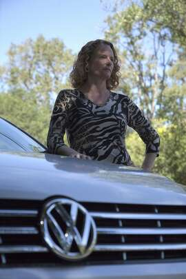 Breese Berkowitz, pictured with her 2015 Volkswagen Passat TDI, Sunday, Oct. 4, 2015, in Walnut Creek, Calif. Berkowitz bought the vehicle just six days before regulators announced that VW had monkeyed with its cars to pass emissions tests.