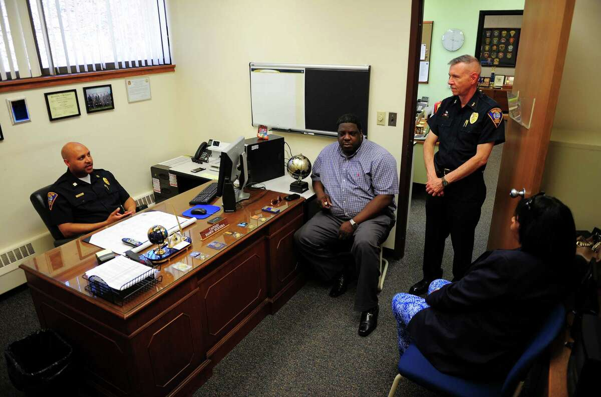 Shelton Police Department's Captain and soon-to-be acting chief Shawn Sequeira, left, at police headquarters in Shelton, Conn., with retiring Chief Joel Hurliman, standing and Greg Johnson, head of the Valley NAACP and Hurliman, and Emma Brooks, chair of the Bridgeport NAACP Freedom Fund, at right. .