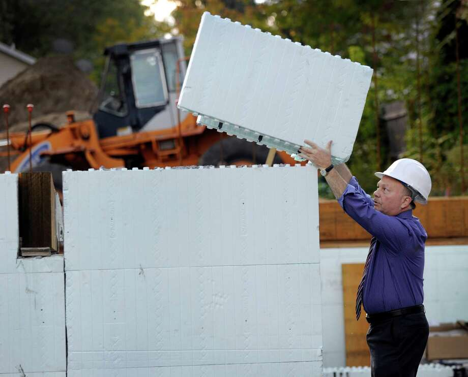 Architect Leigh Overland demonstrates how polystyrene foam blocks fit together to form walls on a building his firm is building at 48 Main Street in Danbury, Monday, Oct. 5, 2015. Photo: Carol Kaliff / Hearst Connecticut Media / The News-Times