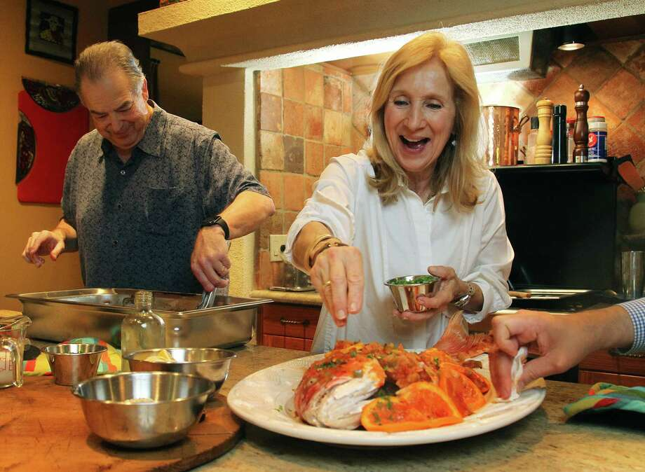 Jim and Diane Gossen put the finishing touches on a whole snapper in their home kitchen. Photo: Mark Mulligan, Staff / © 2015 Houston Chronicle