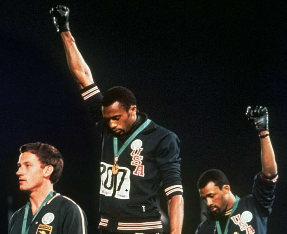 """U.S. Olympians Tommie Smith, center, and John Carlos, right, give the black pride salute during the playing of the """"Star Spangled Banner"""" after Smith received the gold medal and Carlos the bronze medal for the 200-meter run at the Summer Olympic Games in Mexico City in this Oct. 16, 1968, file photo. Photo: /AP / AP"""