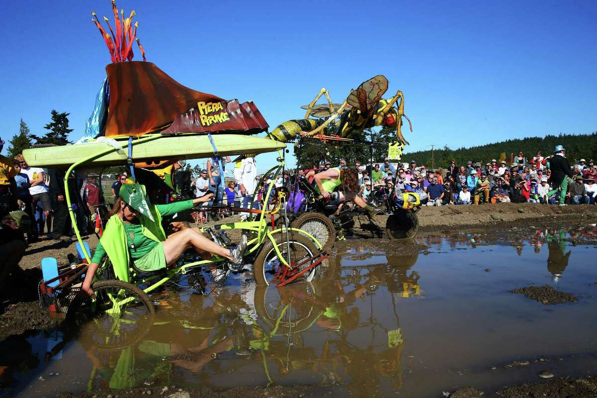 Teams Ptera Ptrike and the Wasp struggle their way through the mud bog during the 33rd annual Great Port Townsend Kinetic Sculpture Race, Sunday, October 4, 2015. Contestants navigated roads, water, sand and other obstacles through Port Townsend in their own human powered sculptures during the two day race.