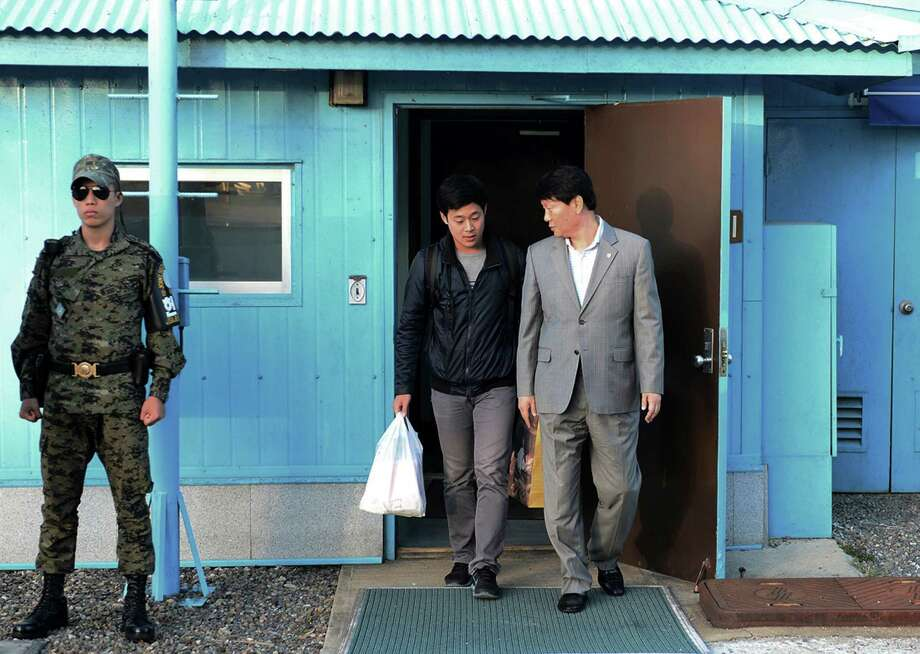 In this photo provided by the South Korean Unification Ministry, South Korean Won Moon Joo, center, who has a permanent resident status in the United States, is escorted by a South Korean official at the border village of Panmunjom in Paju, South Korea, Monday, Oct. 5, 2015. North Korea freed a South Korean national who'd been attending New York University before his detention, Seoul officials said Monday, in a possible sign Pyongyang wants better ties with rival Seoul and may back away from a recent threat to launch a long-range rocket later this month. (The South Korean Unification Ministry via AP) Photo: HOGP / The South Korean Unification Min
