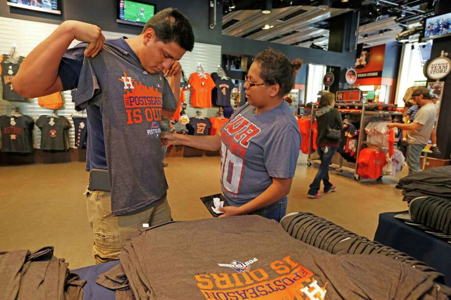 Leonardo Lopez gets advice from his girlfriend, Nancy Viera, as they pick out Astros T-shirts on Monday at Minute Maid Park. Astros fans whisked thousands of special postseason T-shirts off the shelves in quick order. Photo: Steve Gonzales, Staff / © 2015 Houston Chronicle