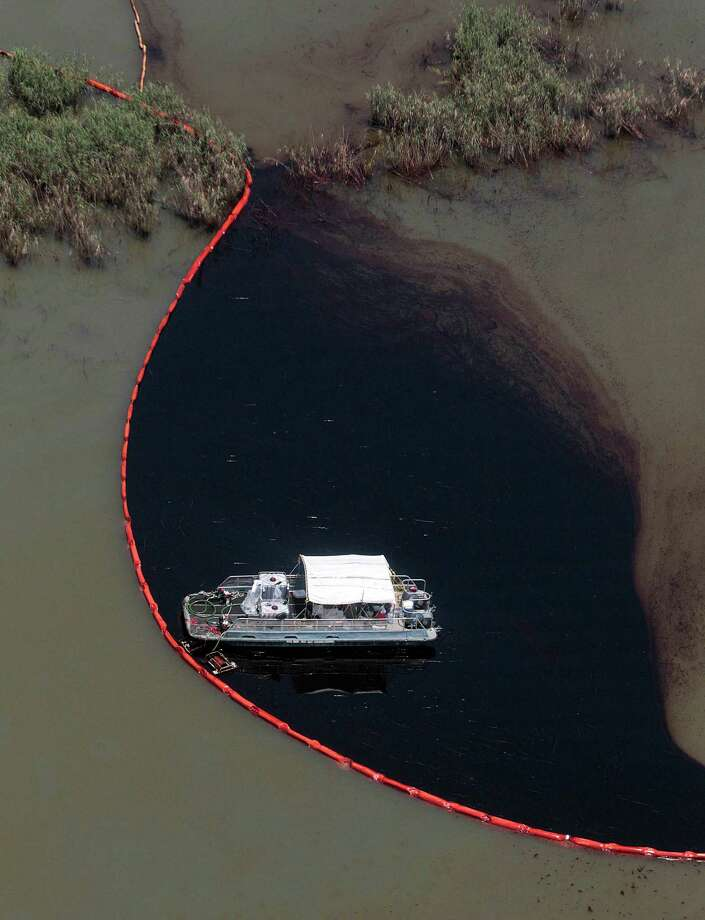 British oil company BP has agreed to pay a record $20.8 billion to resolve government claims arising from the 2010 Deepwater Horizon disaster that coated the Gulf Coast with oil. Here, workers use boom to contain spilled crude in Pass a Loutre, Louisiana (AP Photo) Photo: Jae C. Hong, STF / AP