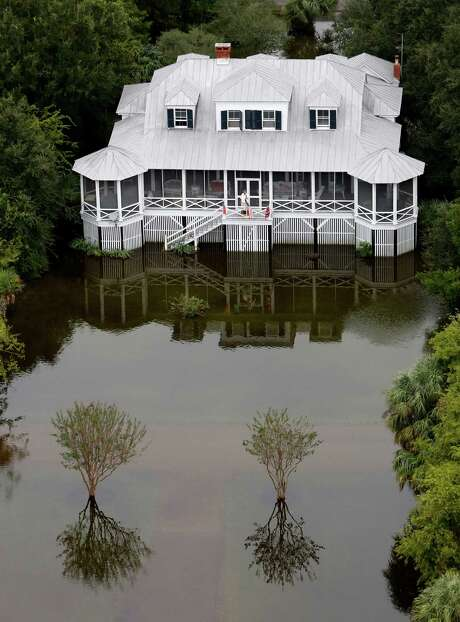 A man talks on his phone on his porch as floodwaters surround his home on Sullivan's Island, S.C. Photo: Mic Smith /Associated Press / FR2 AP