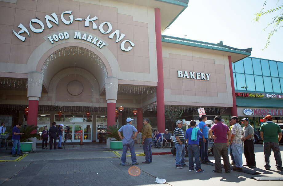 Customers wait outside Hong Kong Food Market on Monday after the store was closed because of a shooting. Police say an employee shot and killed his supervisor, then himself in an apparent murder-suicide. Photo: Cody Duty, Staff / © 2015 Houston Chronicle