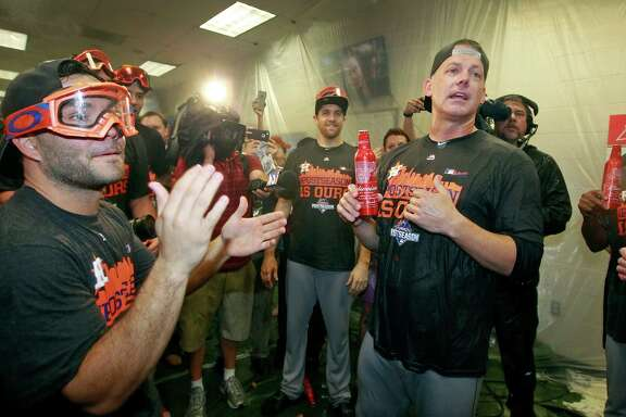 Houston Astros manager A.J. Hinch, right, speaks to Jose Altuve, left, and the team during a celebration of their AL wild card playoff berth despite losing 5-3 to the Arizona Diamondbacks during a baseball game, Sunday, Oct. 4, 2015, in Phoenix.