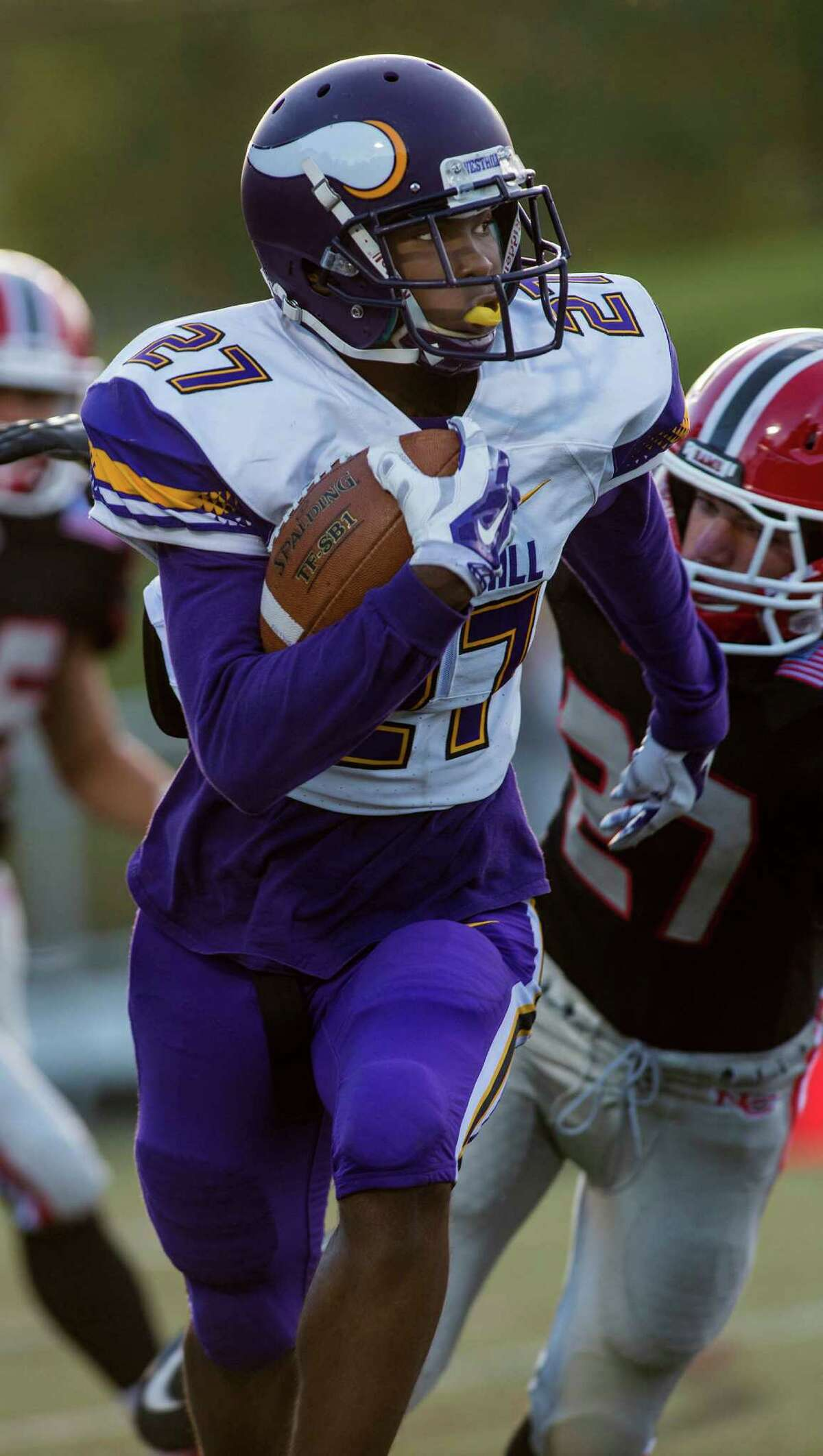 Westhill High School's Everett Charles Brown runs with the ball against New Canaan High School on Monday.