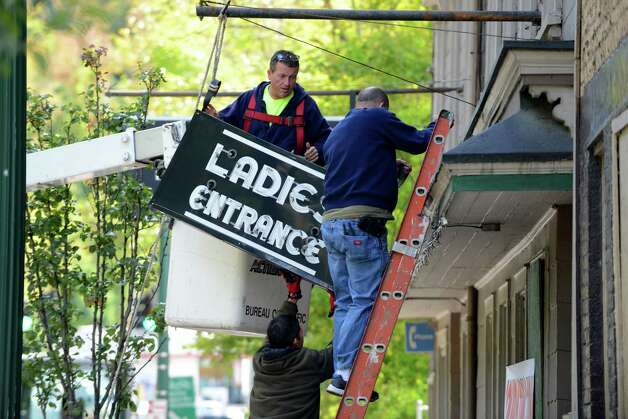 "The iconic South End Tavern ""Ladies Entrance"" sign is removed by workers from the City of Troy Monday afternoon, Oct. 5, 2015,on Burden Ave in Troy, N.Y. The Rensselaer County Historical Society raised money to purchase both of  the building's signs. (Will Waldron/Times Union) Photo: Will Waldron / 10033629A"