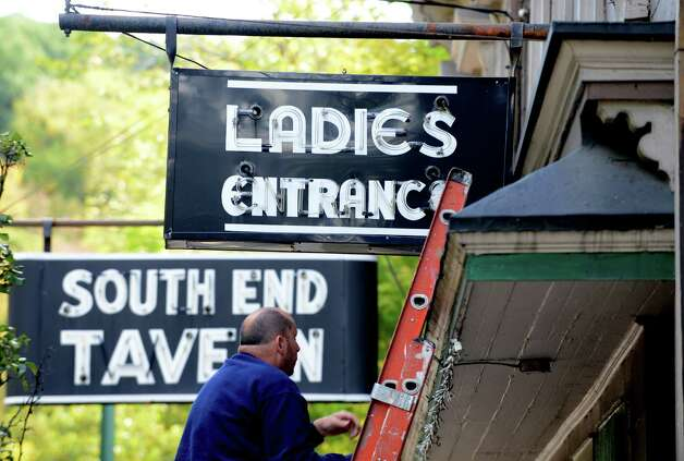 The iconic South End Tavern signs are removed by workers from the City of Troy Monday afternoon, Oct. 5, 2015, on Burden Ave in Troy, N.Y. The Rensselaer County Historical Society raised money to purchase the signs. (Will Waldron/Times Union) Photo: Will Waldron / 10033629A