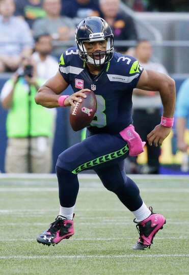 Seattle Seahawks quarterback Russell Wilson scrambles as he looks to pass in the first half of an NF