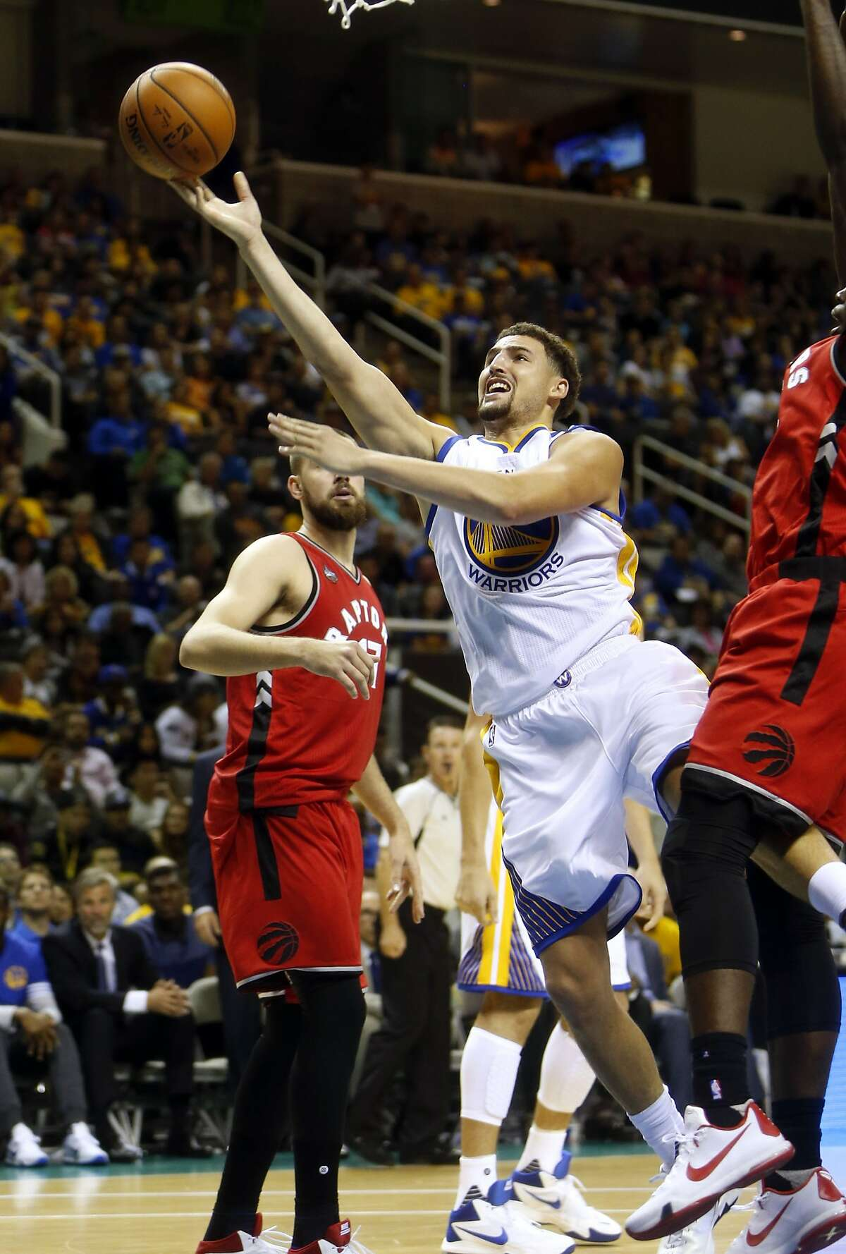 Golden State Warriors' Klay Thompson scores against Toronto Raptors in 1st quarter during NBA preseason game at SAP Center in San Jose, Calif., on Sunday, October 5, 2015.