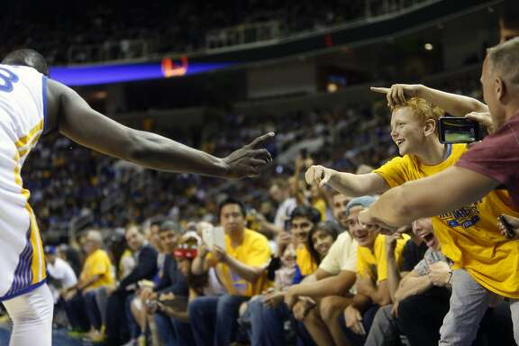 Golden State Warriors' fans celebrate with Draymond Green in 2nd quarter against Toronto Raptors during NBA preseason game at SAP Center in San Jose, Calif., on Sunday, October 5, 2015.