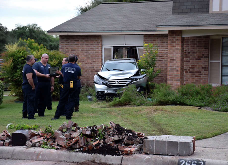 A Honda SUV was pushed backward into a house at the intersection of Pebble Peak and Forest Pebble on the North Side by a driver who is expected to face aggravated assault charges. Photo: Mark D. Wilson /San Antonio Express-News / San Antonio Express-News