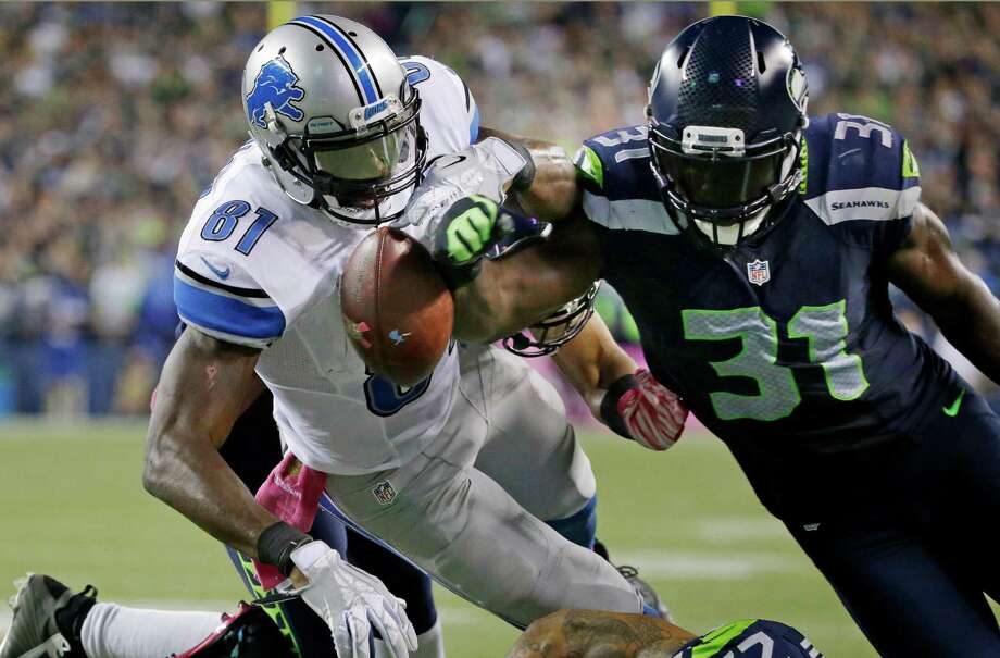 Seahawks safety Kam Chancellor (31) separates the ball from Lions receiver Calvin Johnson during a pivotal play in the fourth quarter in Seattle's win. Photo: Elaine Thompson, STF / AP
