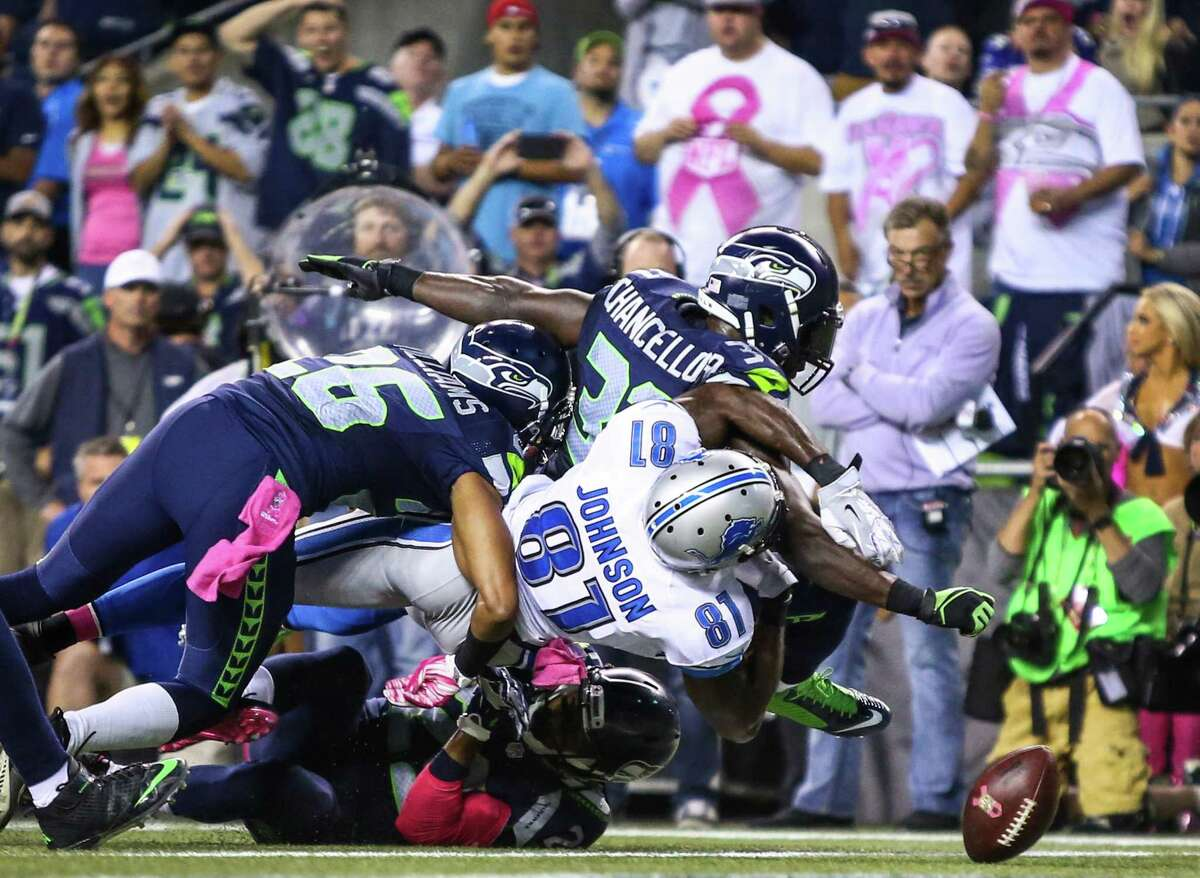Seattle Seahawks player Kam Chancellor punches the ball out of the hands of Detroit Lions player Calvin Johnson at the goal line during Monday Night Football on Monday, October 5, 2015. The Seahawks beat the Lions 13-10.