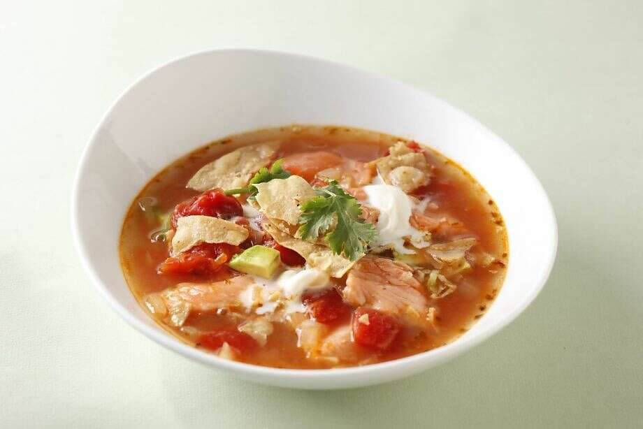 This riff on the traditional chicken tortilla soup is a great way to stretch expensive salmon. The broth cooks the raw salmon right in the bowl, which saves time and keeps the fish tender. Photo: Craig Lee / Special To The Chronicle