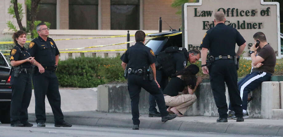 A woman crouches down (center) Tuesday October 6, 2015 at French and San Pedro after police were called to a situation that may involve a man with a gun. Photo: John Davenport, San Antonio Express-News / ©San Antonio Express-News/John Davenport