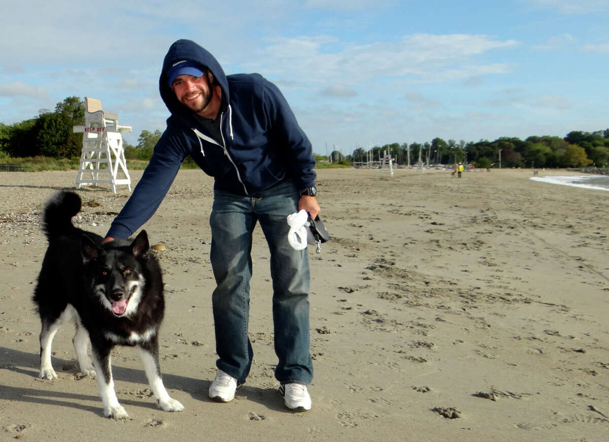 Brian Dolan visits Jennings Beach with his dog, Juno, on Sunday morning.