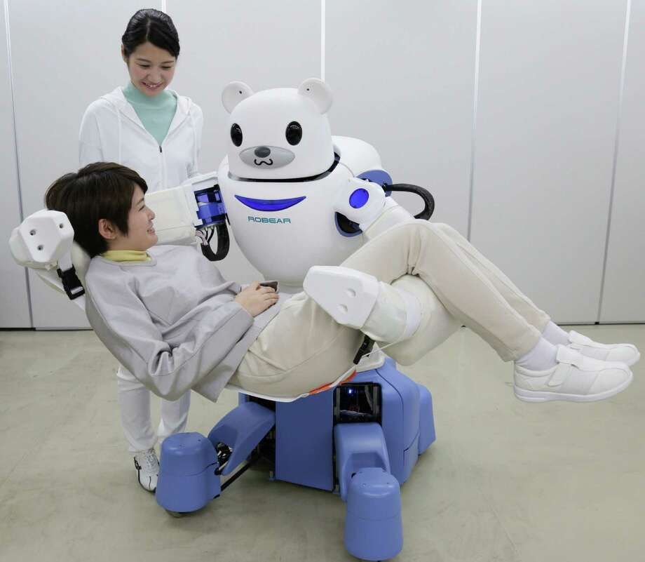 """Judson ISD teacher Joseph Jacobson says anyone curious about the future of robotics should look to Japan. This picture taken on Feb. 23, 2015, shows a polar bear robot """"Robear"""" lifting a woman for a demonstration in Nagoya, central Japan. The """"Robear,"""" developed by Riken Institute and Sumitomo Riko, has a polar cub-like face with big doey eyes, but packs enough power to transfer frail patients from a wheelchair to a bed or a bath. Photo: Jiji Press /AFP / Getty Images / AFP"""