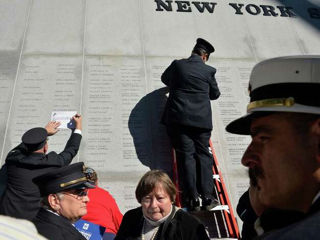 Firefighters, families and friends take rubbings at New York State Firefighters Memorial on the Empire State Plaza Tuesday Oct. 6, 2015 in Albany, NY.  (John Carl D'Annibale / Times Union) Photo: John Carl D'Annibale / 10033635A