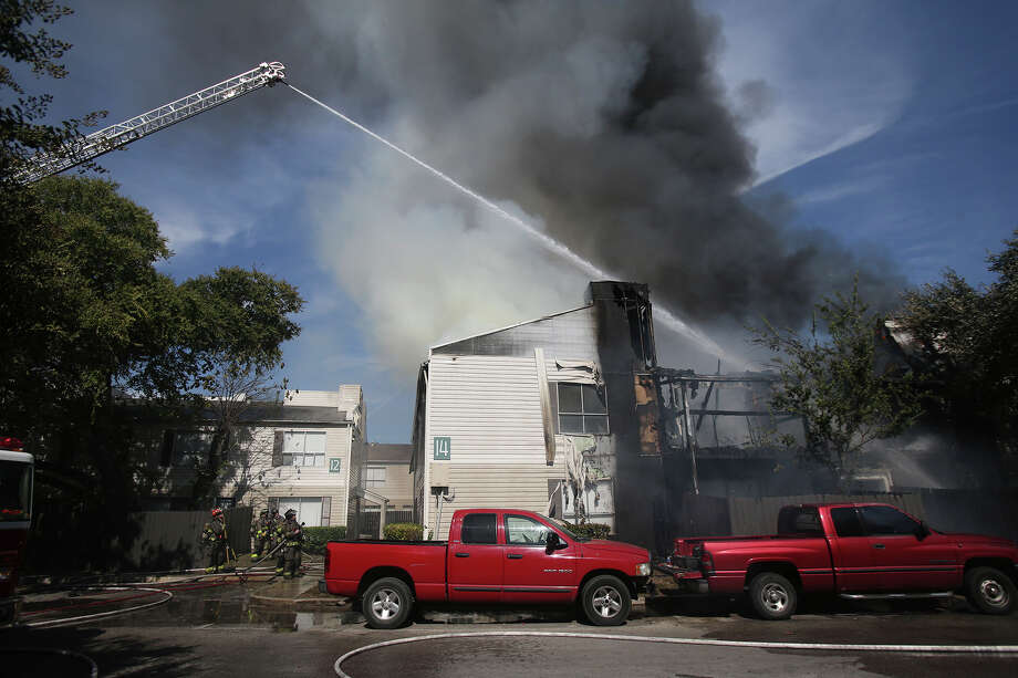 San Antonio firefighters douse flames Tuesday October 6, 2015 at the Fox Run Apartments on the 10,000 block of Broadway. the Two alarm fire started shortly before 11:00 am. Photo: John Davenport, San Antonio Express-News / ©San Antonio Express-News/John Davenport