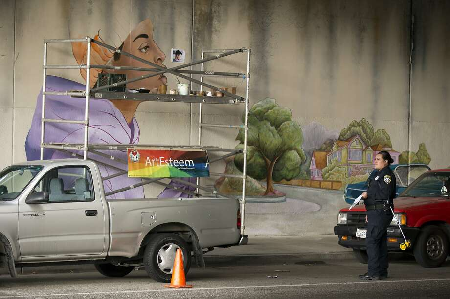 An evidence technician waits to measure the scene of a fatal shooting in the 3500 block of West Street, beneath Interstate 580, Tuesday, Sept. 29, 2015, in Oakland, Calif. Oakland Police officials say an artist working on a community mural in a freeway underpass was shot and killed after an apparent argument with the shooter.  (D. Ross Cameron/Oakland Tribune via AP) MANDATORY CREDIT Photo: D. Ross Cameron, Associated Press