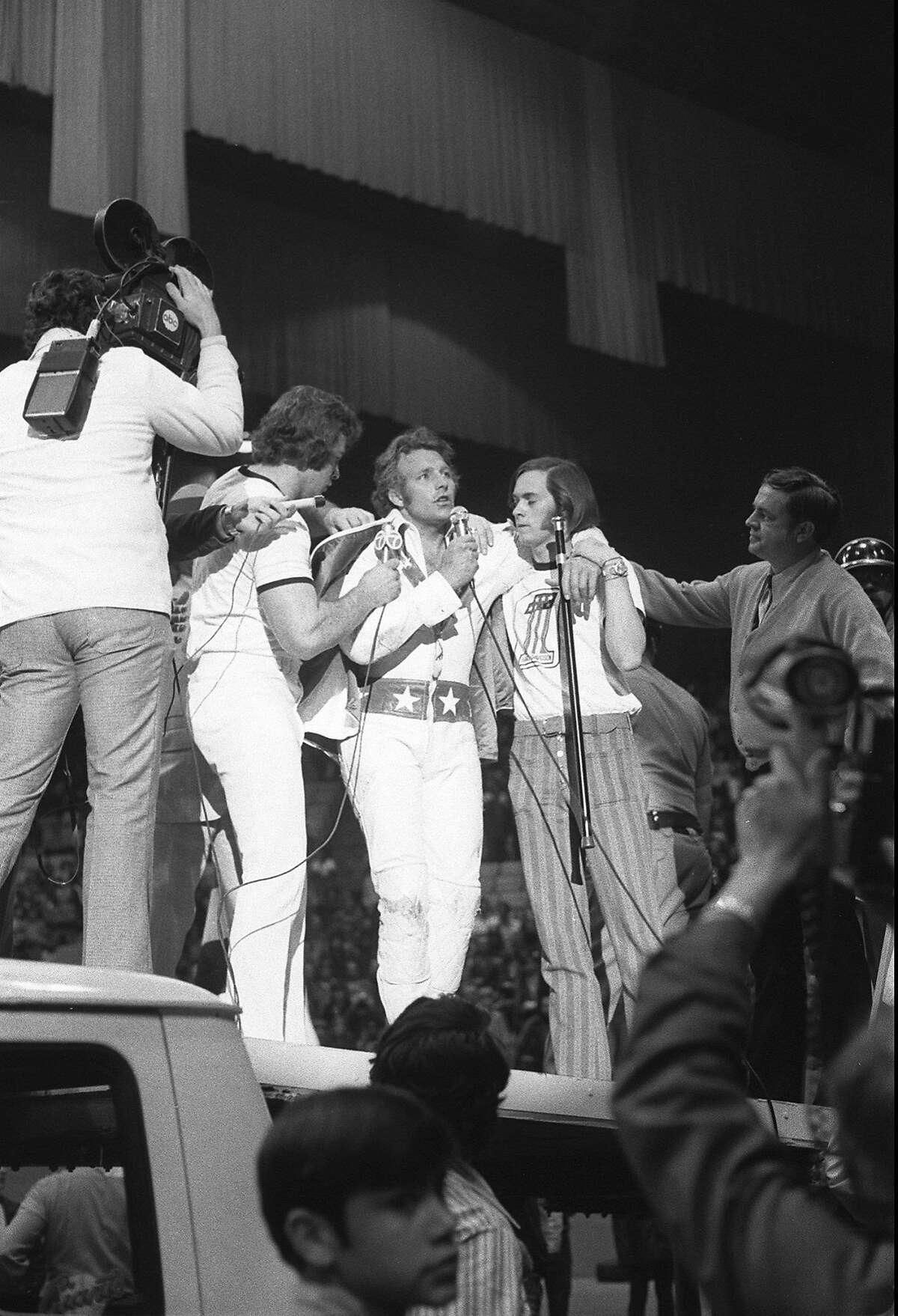 Evel Knievel addresses the crowd at the Cow Palace after making his record jump.
