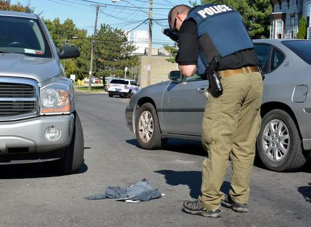 An Albany police photographer stands over sweatshirt at the scene of a stabbing on Manning Boulevard. (John Carl D'Annibale / Times Union)