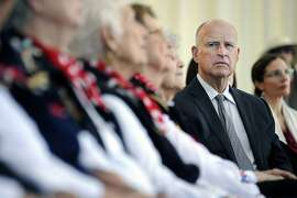 Governor Jerry Brown looks on as he sit next to a row of Rosie the Riveters during a ceremony for held the signing of California Fair Pay Act Ð SB 358, in the Craneway Pavilion at Rosie the Riveter-WWII Home Front National Historical Park in Richmond, CA Tuesday, October 6, 2015.