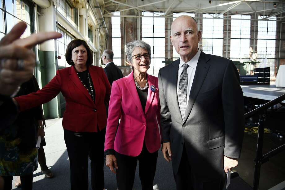 Gov. Jerry Brown stands with Sen. Hanna-Beth Jackson, D-Santa Barbara, author of the California Fair Pay Act, following Brown's signing of the bill into law during a ceremony held in the Craneway Pavilion at Rosie the Riveter-WWII Home Front National Historical Park in Richmond on Oct. 6, 2015. Photo: Michael Short, Special To The Chronicle