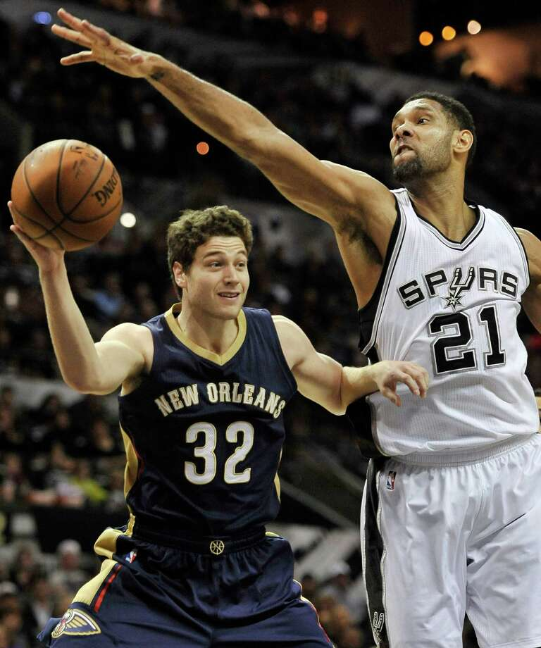 New Orleans Pelicans guard Jimmer Fredette (32) looks to pass around San Antonio Spurs forward Tim Duncan in the second half of an NBA basketball game, Wednesday, Dec. 31, 2014, in San Antonio. San Antonio won 95-93 in overtime. (AP Photo/Darren Abate) Photo: Darren Abate, FRE / Associated Press / FR115 AP