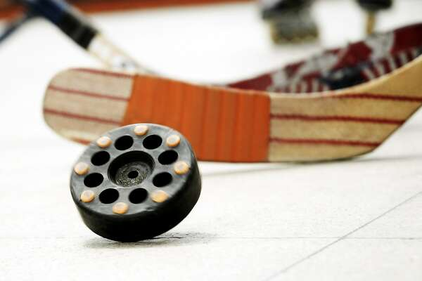 Close-up of a hockey puck with an ice hockey stick