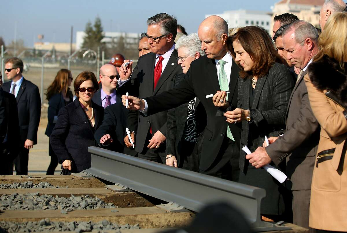 Gov. Jerry Brown, center, and his wife Anne Gust, third from right, start signing a portion of the rail at the California High Speed Rail Authority ground breaking event Tuesday, Jan. 6, 2015, in Fresno, Calif. California's high-speed rail project has become the first in the nation to break ground. Tuesday's groundbreaking was attended by several hundred people who gathered near old rail lines in an industrial section of downtown Fresno.