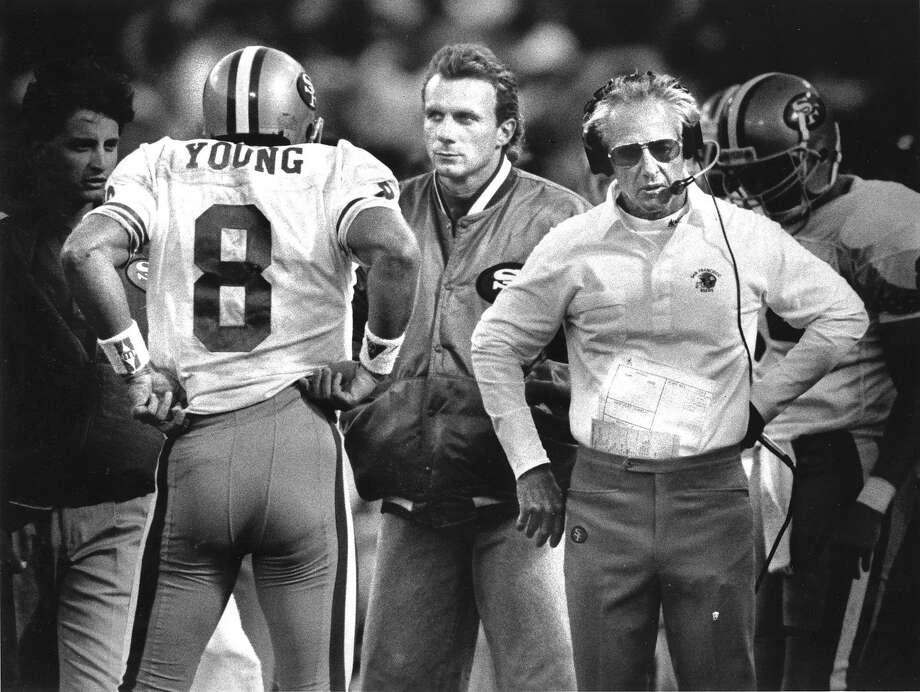 San Francisco 49er Steve Young talks to Joe Montana and George Seifert on the sidelines  Photo shot 08/31/1990 Photo ran 09/171991, p. D1 Photo: Scott Sommerdorf, The Chronicle