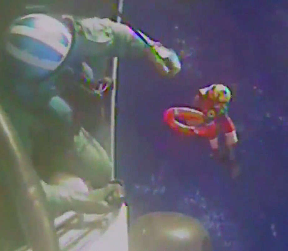 In this Sunday, Oct. 4, 2015 photo made from video and released by the U.S. Coast Guard, a Coast Guard crew member is moved back to the helicopter after investigating a life boat, that was found from the missing ship El Faro. On Monday, four days after the ship vanished, the Coast Guard concluded it sank near the Bahamas in about 15,000 feet of water. One unidentified body in a survival suit was spotted, and the search went on for any trace of the other crew members. The search continued Tuesday, Oct. 6, 2015. (U.S. Coast Guard via AP) Photo: HOGP / U.S. Coast Guard