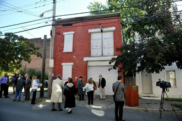 Officials from the city of Albany and Albany County along with residents gather outside of 108 Broad St., for a press conference on Tuesday, Oct. 6, 2015, in Albany, N.Y.  The press conference was held by the Albany County Land Bank to announce the sale of two properties in the South End to residents.  108 Broad St. and 63 Delaware St. are the two locations the Land Bank has sold.   (Paul Buckowski / Times Union) Photo: PAUL BUCKOWSKI / 10033633A