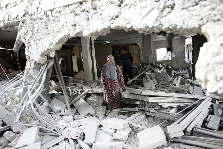 A Palestinian woman walks amid the rubble of a house Tuesday after Israeli security forces demol-ished the homes of two Palestinians behind attacks. Photo: THOMAS COEX, Staff / AFP