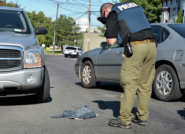 A police photographer stands over a sweatshirt at the scene of a stabbing on Manning Blvd. Tuesday Oct. 6, 2015 in Albany, NY. (John Carl D'Annibale / Times Union) Photo: John Carl D'Annibale
