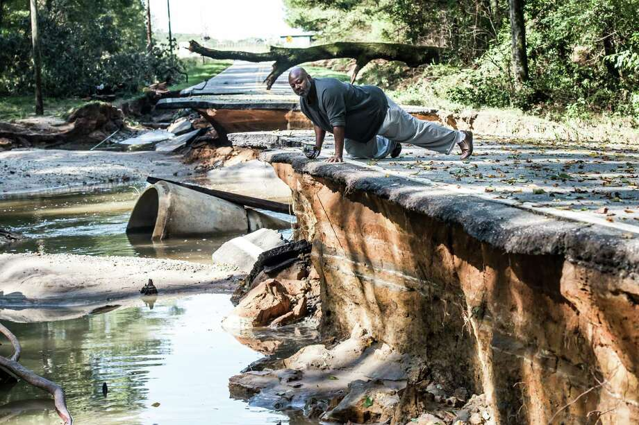 Trey McMillian looks at the damage caused by flooding on a road in Eastover, S.C. Water mains are broken, roads and bridges are out, and the potable water supply remains seriously compromised in South Carolina's capital, Columbia. Photo: Sean Rayford /Getty Images / 2015 Getty Images