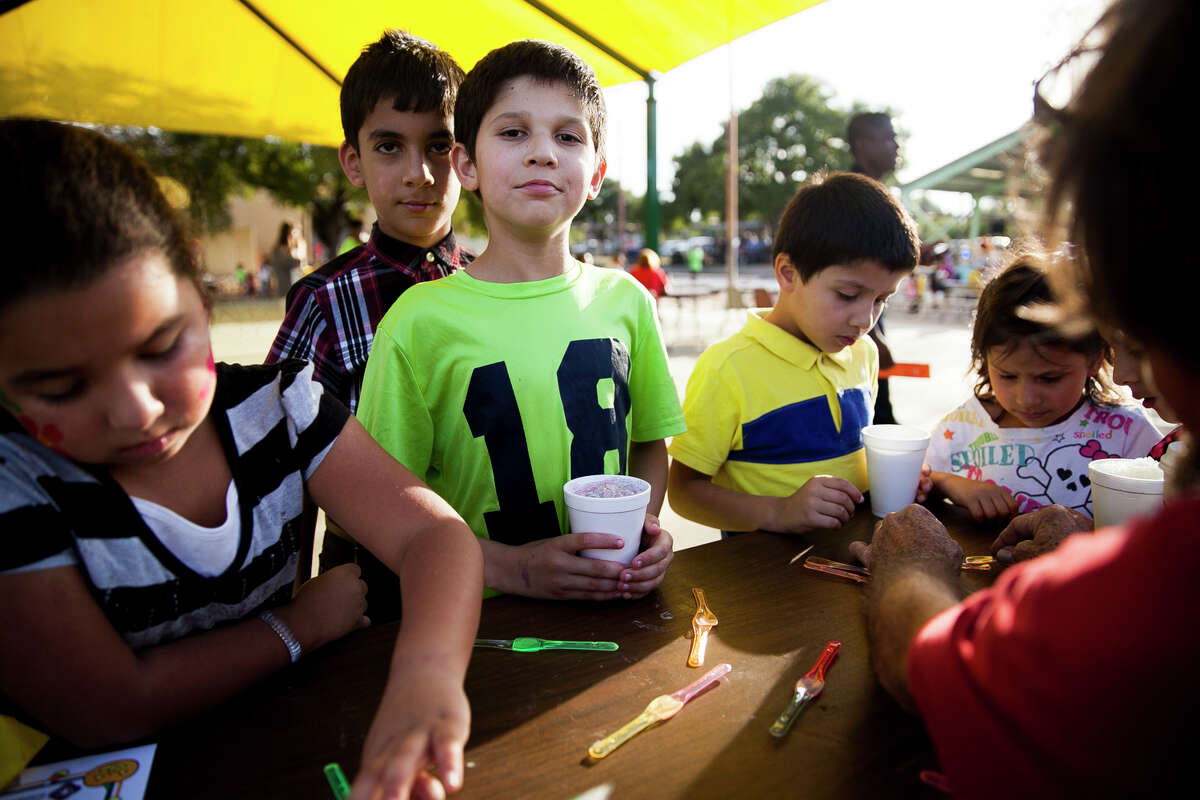 (Center) Gherat, 9, and his friend Zabi Azizi, 10, wait to make crafts Tuesday Oct. 6, 2015 during National Night Out at West End Hope in Action.