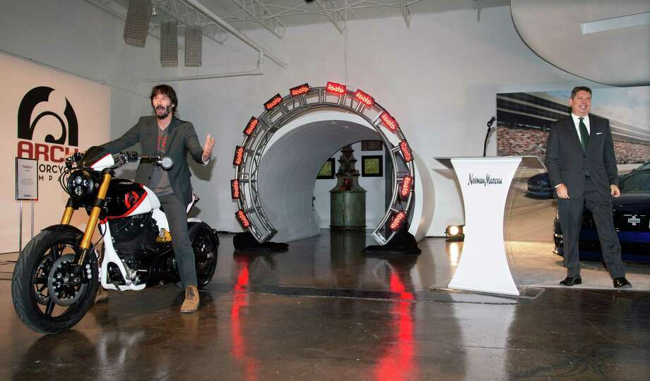In this photo provided by Neiman Marcus, actor and Arch Motorcycles co-owner Keanu Reeves, left, is introduced by John Koryl, president of Neiman Marcus Stores and Online at Neiman Marcus, as he rides an Arch Motorcycle during the launch of the Neiman Marcus Christmas Book, Tuesday, Oct. 6, 2015 in Dallas. For $150,000, shoppers can buy a package for two that includes a limited edition KRGT-1 motorcycle and a two-day ride in the company of Reeves and Arch co-owner Gard Hollinger. (Tim Sharp/Neiman Marcus via AP) Photo: Tim Sharp, HONS / Associated Press / Neiman Marcus