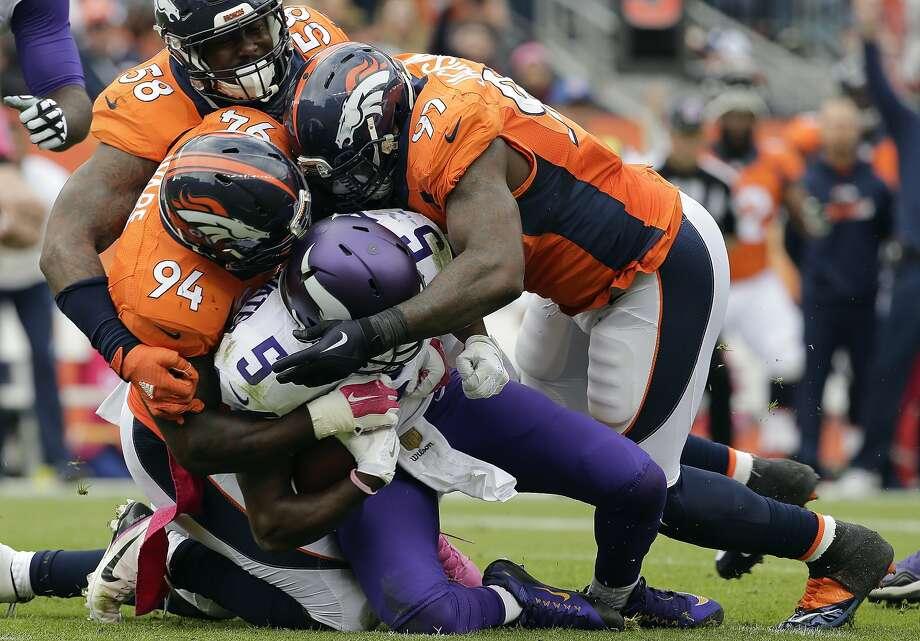 Vikings QB Teddy Bridgewater (5) is gang-sacked by Broncos Von Miller, DeMarcus Ware, Malik Jackson. Photo: Joe Mahoney, Associated Press