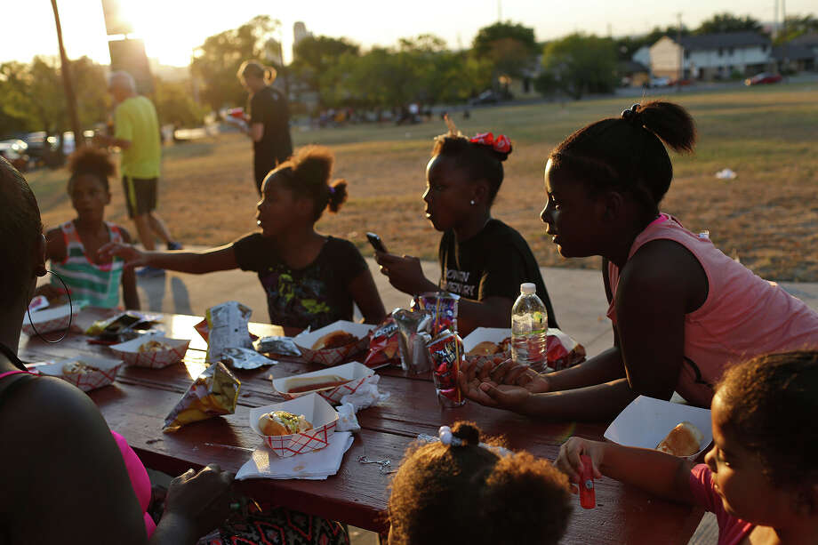 Amorie West, 9, right, with her sister, Q'yree West, 8, left, and friend Makya Webber, 10, eat with family and friends during the National Night Out event with the Dignowity Hill Neighborhood Association at Lockwood Park in San Antonio on Tuesday, Oct. 6, 2015. Photo: Lisa Krantz, San Antonio Express-News / San Antonio Express-News / ©2015 San Antonio Express-News