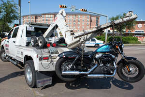 A motorcycle is loaded onto a tow truck after it was involved in a fatal accident involving an SUV along South Voss Road near San Felipe, Tuesday, Oct. 6, 2015, in Houston. The motorcyclist died at the scene after colliding with an SUV.