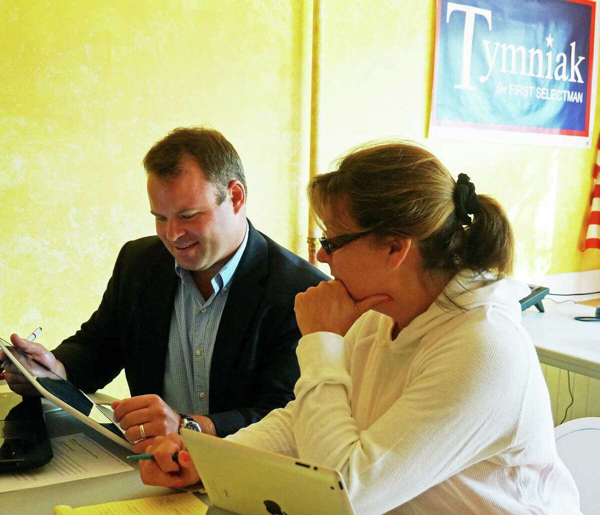 Republican first selectman candidate Chris Tymniak goes over some plans with running mate Laurie McArdle at their Unquowa Road headquarters.
