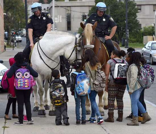 Students at Griffen Elementary School surround a police officer and his horse at during Walk To School Day on Wednesday. The effort aims to get children to walk to school safely. (Skip Dickstein / Times Union)