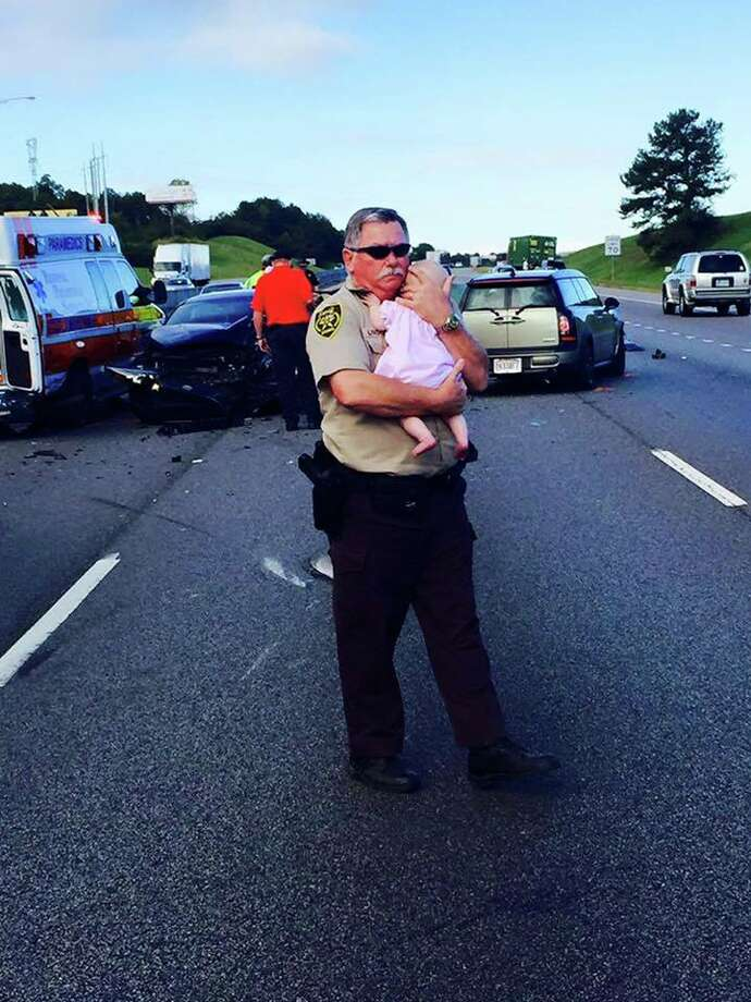 A photo of Jefferson County Deputy Ric Lindley comforting a baby after a car crash on Oct. 5, 2015, has gone viral. Photo: Jefferson County Sheriffs Office